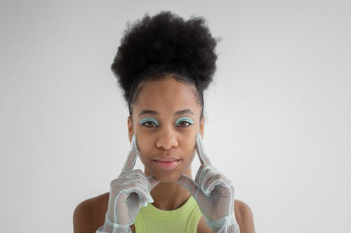 Young African American female model with curly hair and bright eyeshadow on eyelids touching face with hands in blue organza gloves and looking at camera