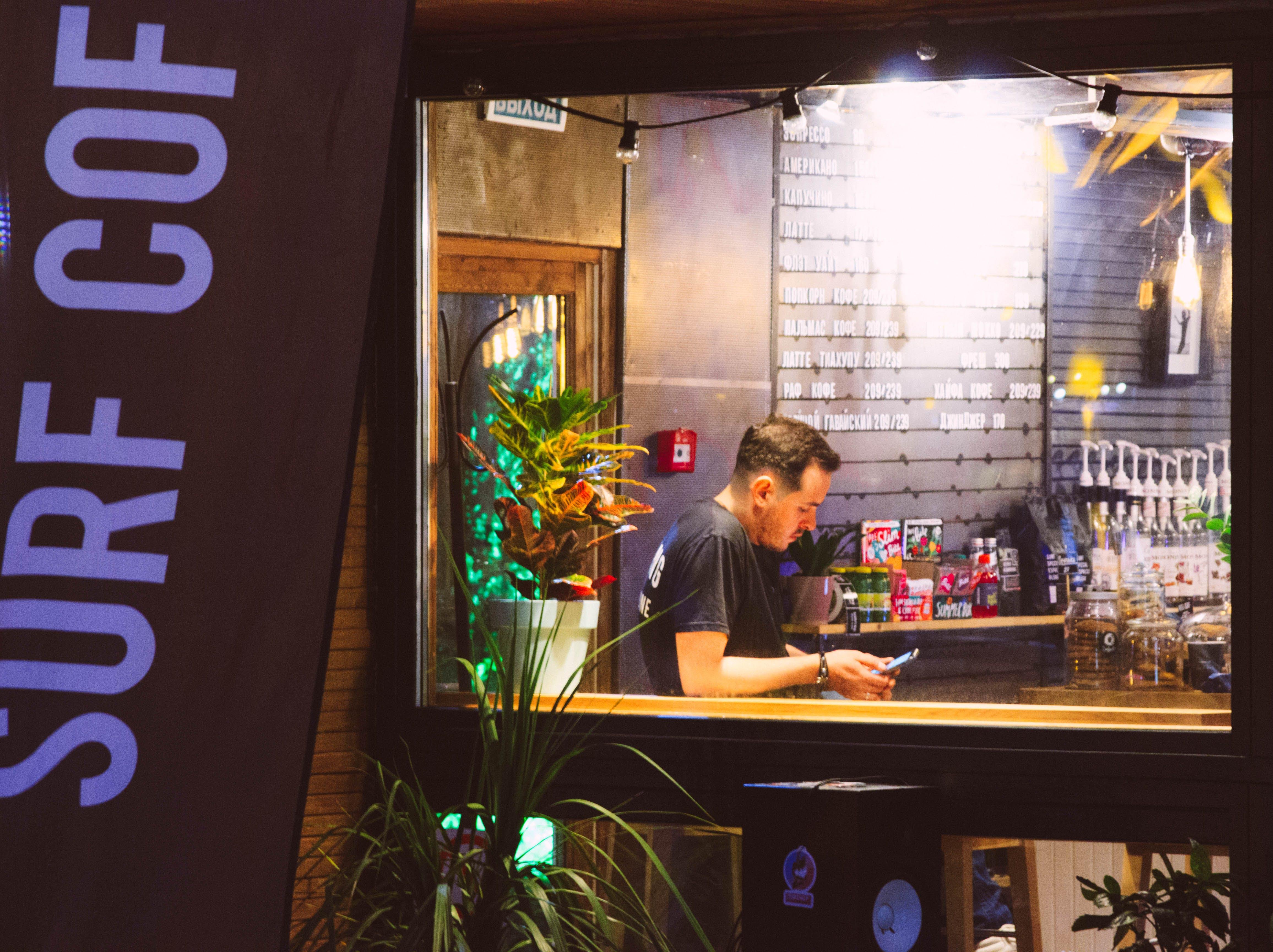 Man Wearing Black Shirt Holding Smartphone Sitting Near Window