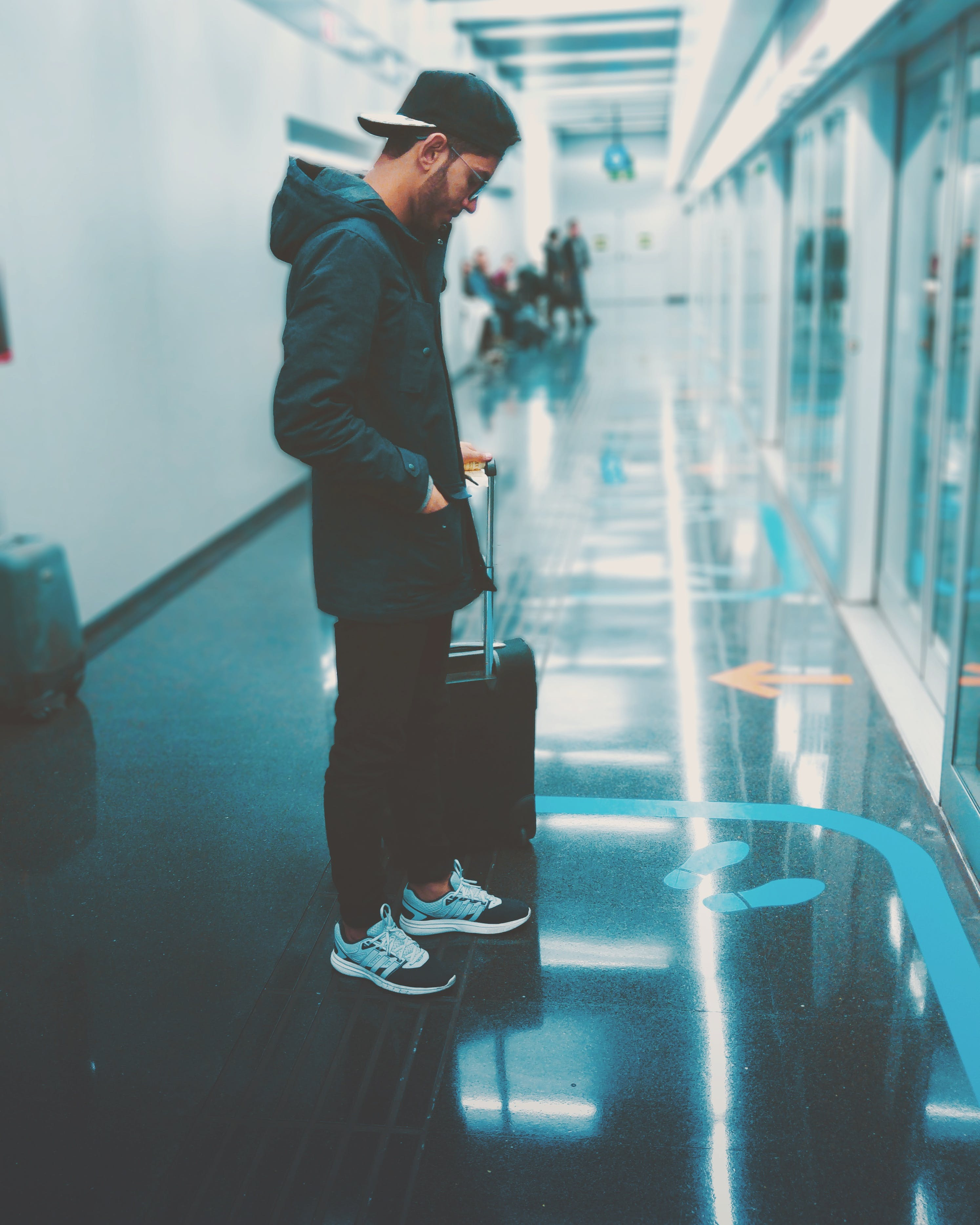 Man Stands Front of Glass Panel While Holding Luggage
