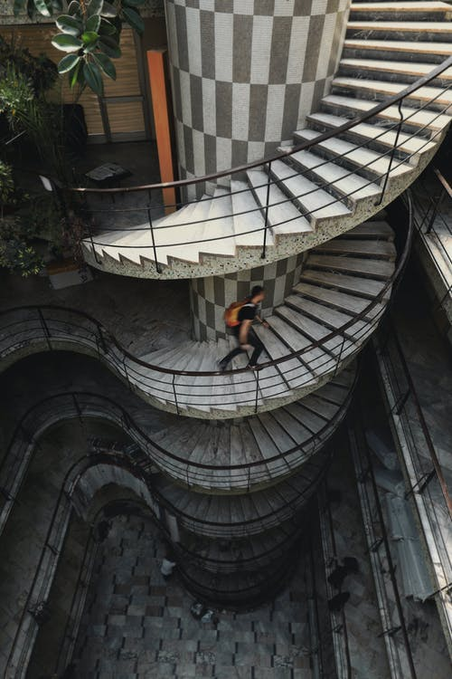 Side view of distant unrecognizable male with backpack walking up spiral staircase with handrail and creative design in modern building