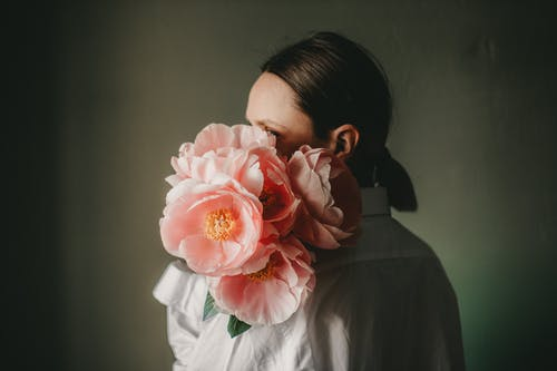 Young female covering face with bouquet of flowers in dark room