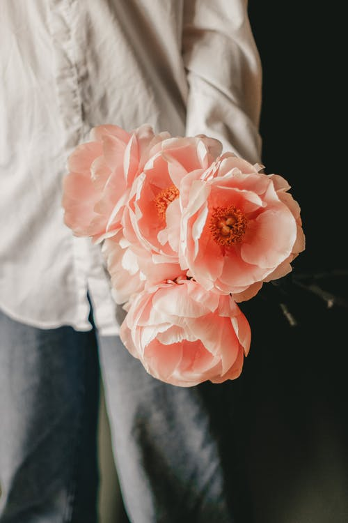 Crop unrecognizable person in casual clothes standing and demonstrating bouquet of fresh pink peonies in daytime