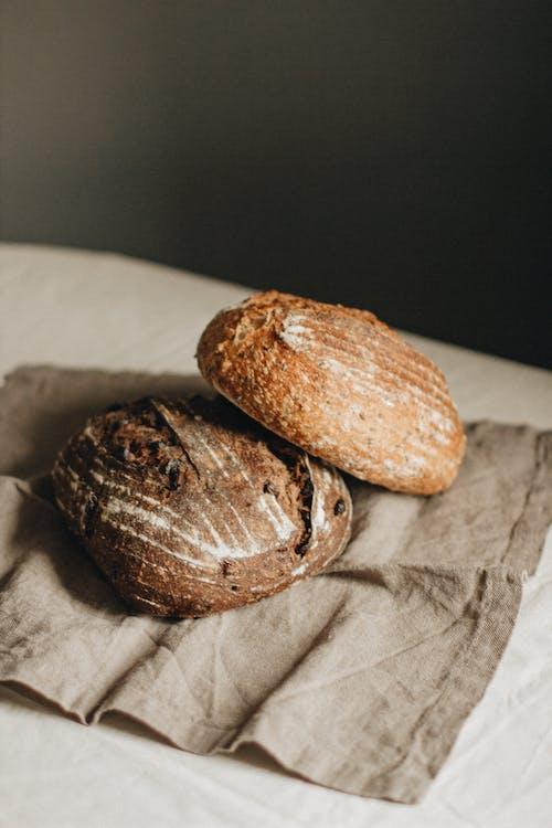 Two Brown Bread on White Textile