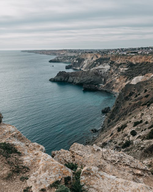 Spectacular rough terrain surrounded with rippling water of ocean under cloudy gray sky