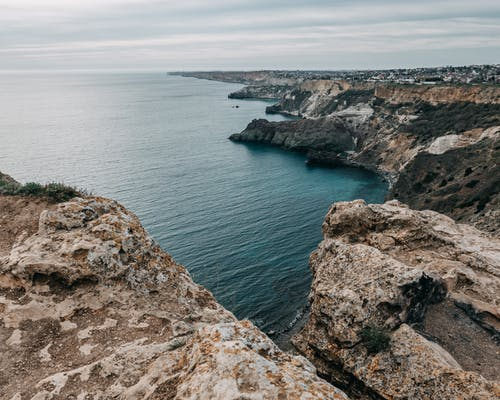 Rough terrain of rocky cliffs washed by rippling water of vast ocean under gray cloudy sky