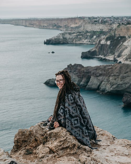 Side view of cheerful young female traveler with long braids in warm poncho and eyeglasses smiling happily while sitting on rocky cliff edge with picturesque sea view