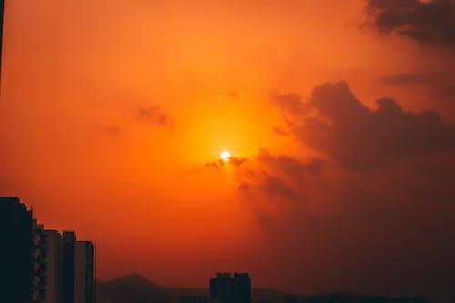 Bright setting sun on dark sky over city