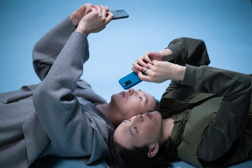 Twins Lying on the Floor while Using Cellphones