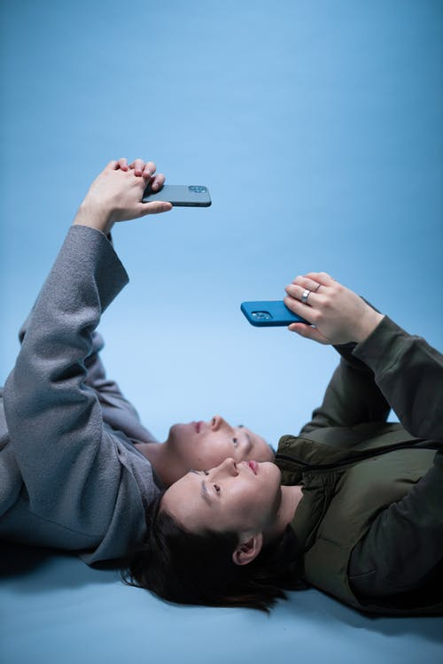 Brothers Lying on the Floor while Using Cellphones