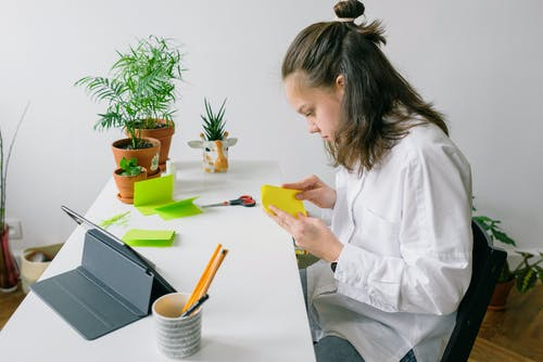 Woman Holding and Folding a Yellow Paper