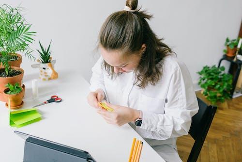 Woman in White Long Sleeve Shirt Folding a Yellow Paper