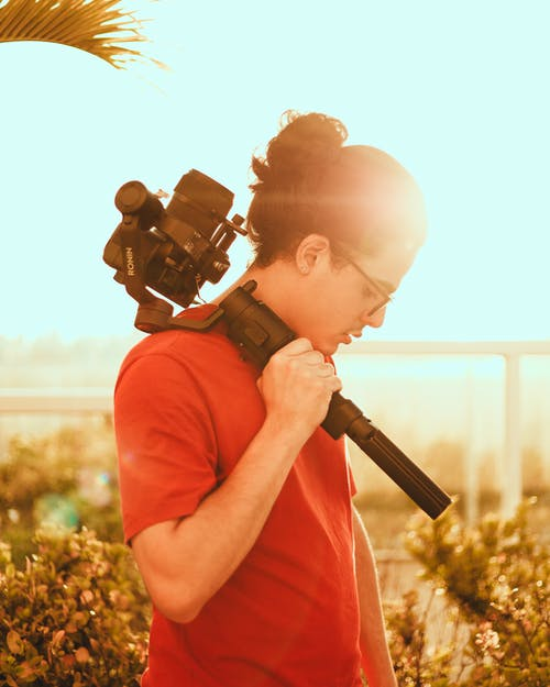 Man in Red T-shirt Holding Black Dslr Camera