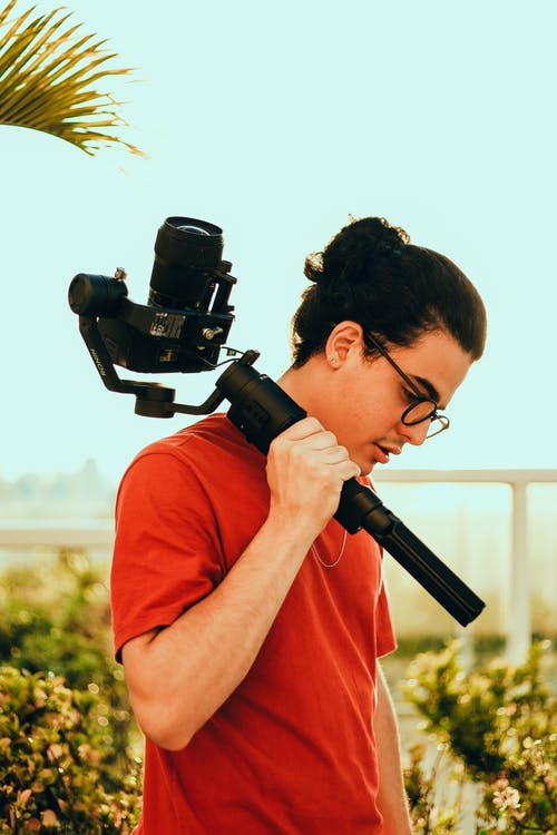 Man in Red Crew Neck T-shirt Holding Black Dslr Camera
