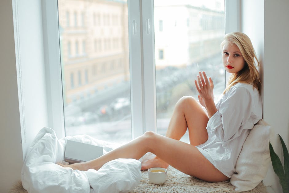 Woman Wearing White Top Sitting Beside Window
