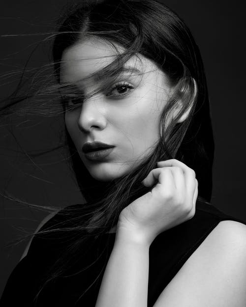 Black and white of young tender female with makeup touching hair while looking at camera