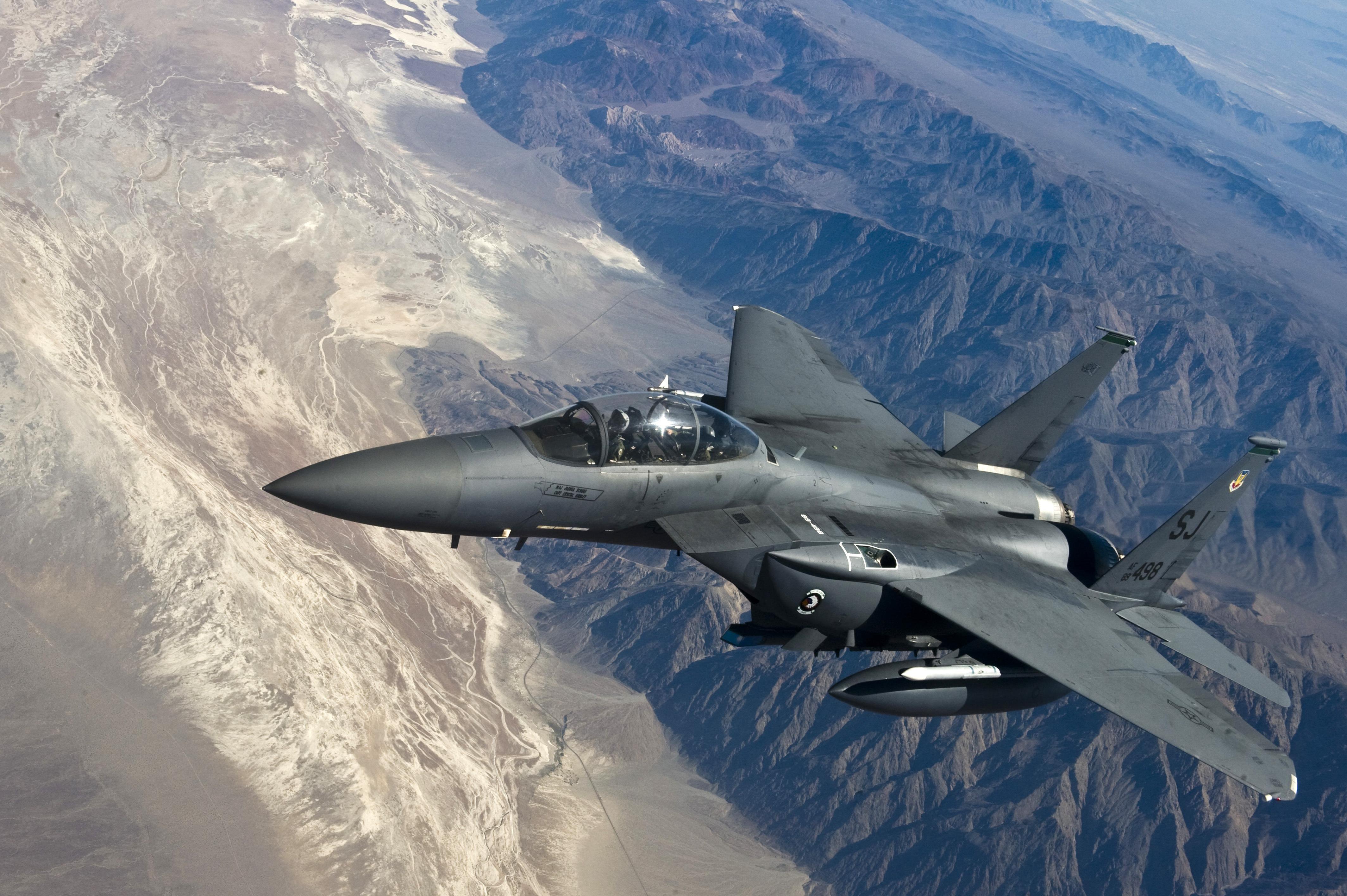 A modern fighter jet flying over mountainous terrain.