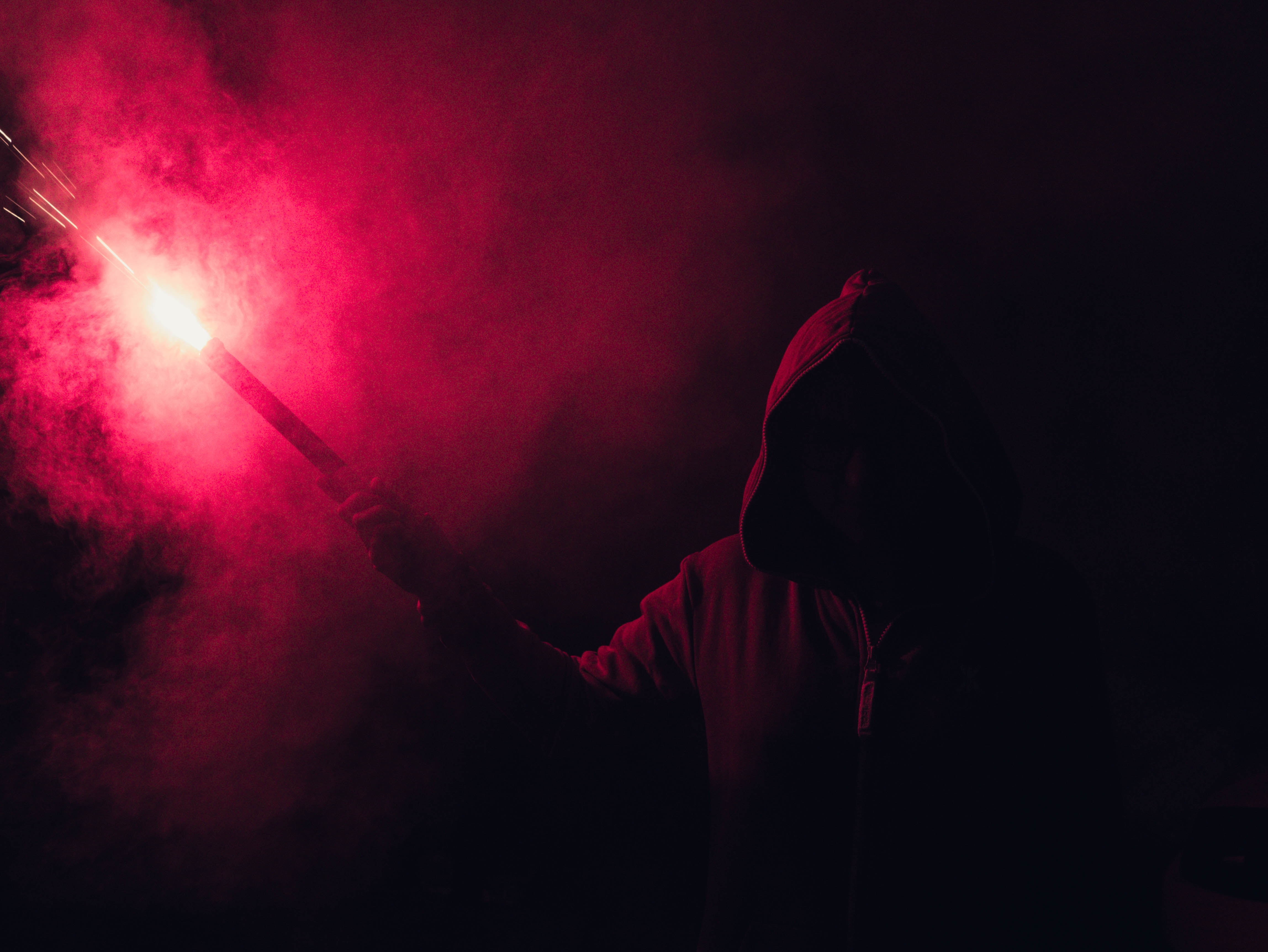 Hooded Figure Holding Red Flare · Free Stock Photo