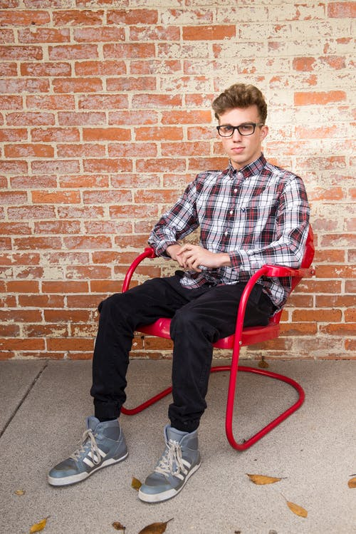 Man Wearing White And Red Long Sleeve Shirt Sitting On Red Steel Armchair