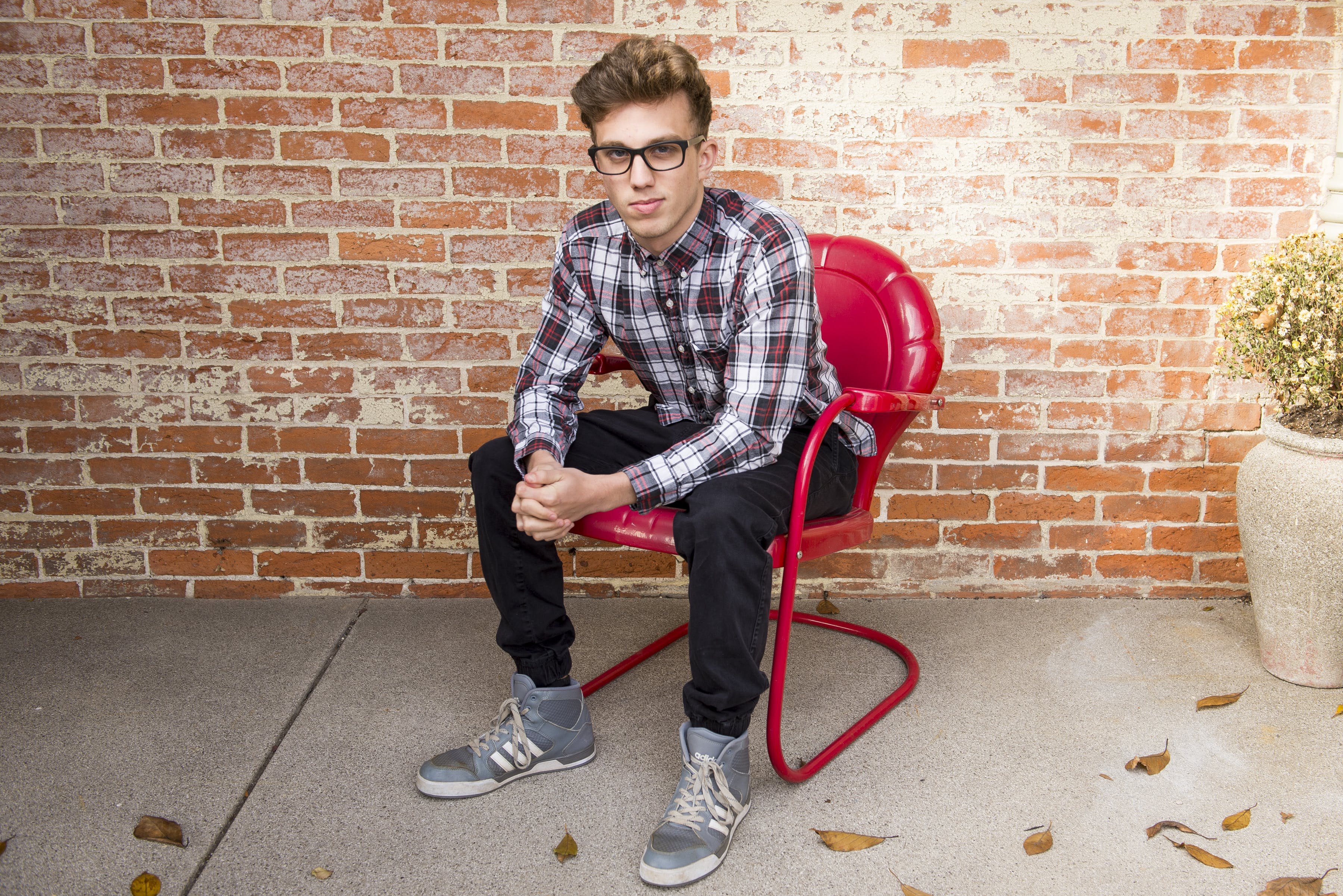 Man In Plaid Long-Sleeved Shirt And Black Pants Sitting On Red Chair