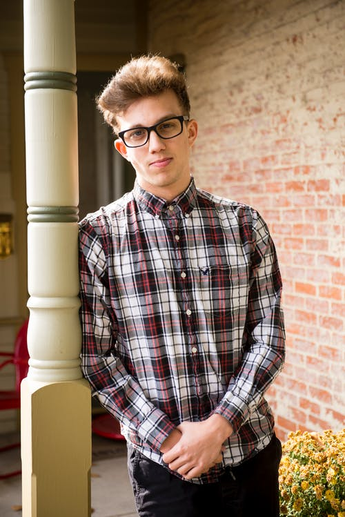 Man in Red and Gray Plaid Dress Shirt With Eyeglasses Leaning on White Concrete Post