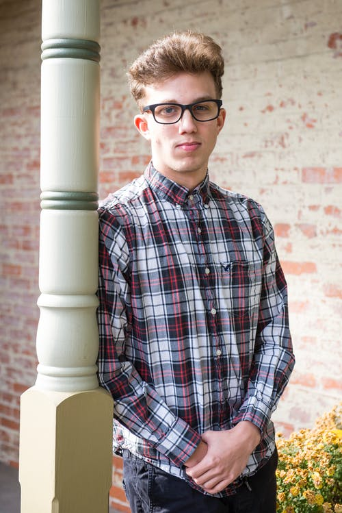Man in Red Black and White Plaid-printed Dress Shirt Wearing Wayfarer Eyeglasses Leaning on White Wooden Post