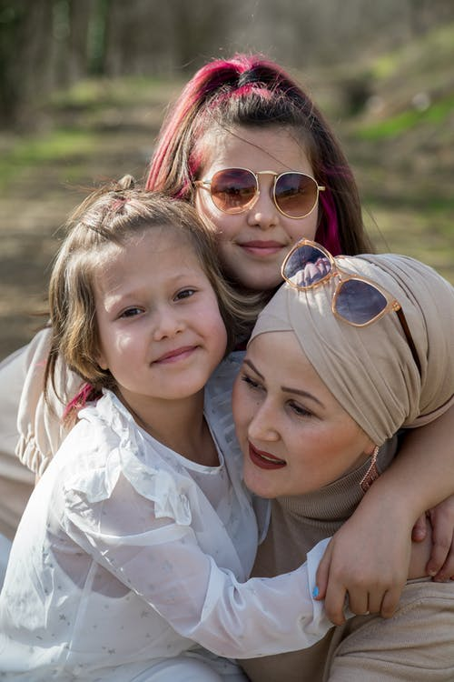 Ethnic mother in traditional headwear with cheerful daughters