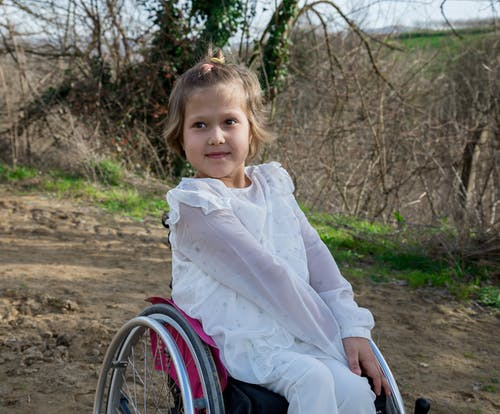 Adorable disabled girl in white clothes looking away while sitting in wheelchair on sandy ground in nature with growing trees