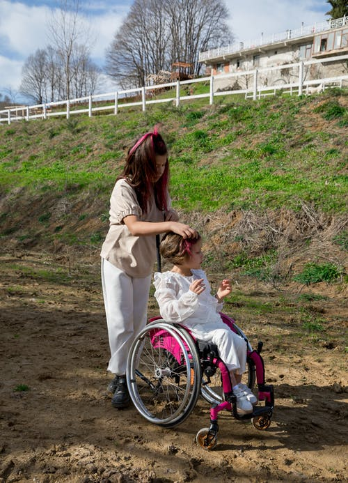 Full body of sister walking with little girl in wheelchair in countryside with green grass and leafless trees in daytime