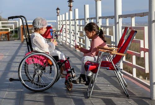 Kırmızı Ve Beyaz Tekerlekli Sandalyede Oturan Kahverengi Gömlekli Kadın