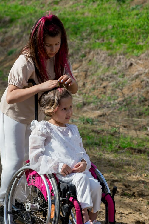 Caring mother touching hair of daughter in wheelchair
