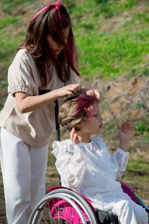 Creative girl touching hair of little sister in wheelchair in park with fresh verdant grass