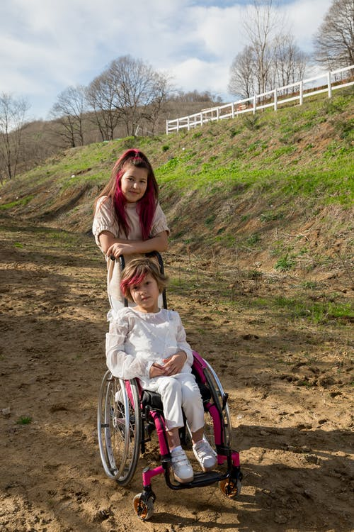 Girl using wheelchair near sister with dyed hair surrounded with slopes with fresh green grass