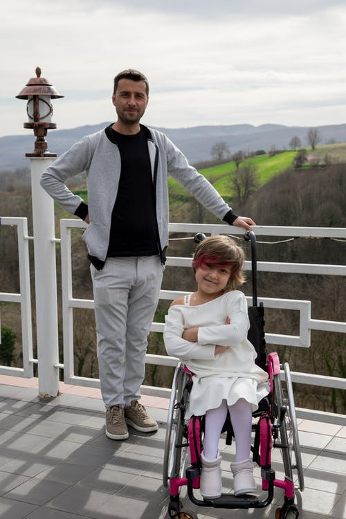 Bearded father near daughter in wheelchair