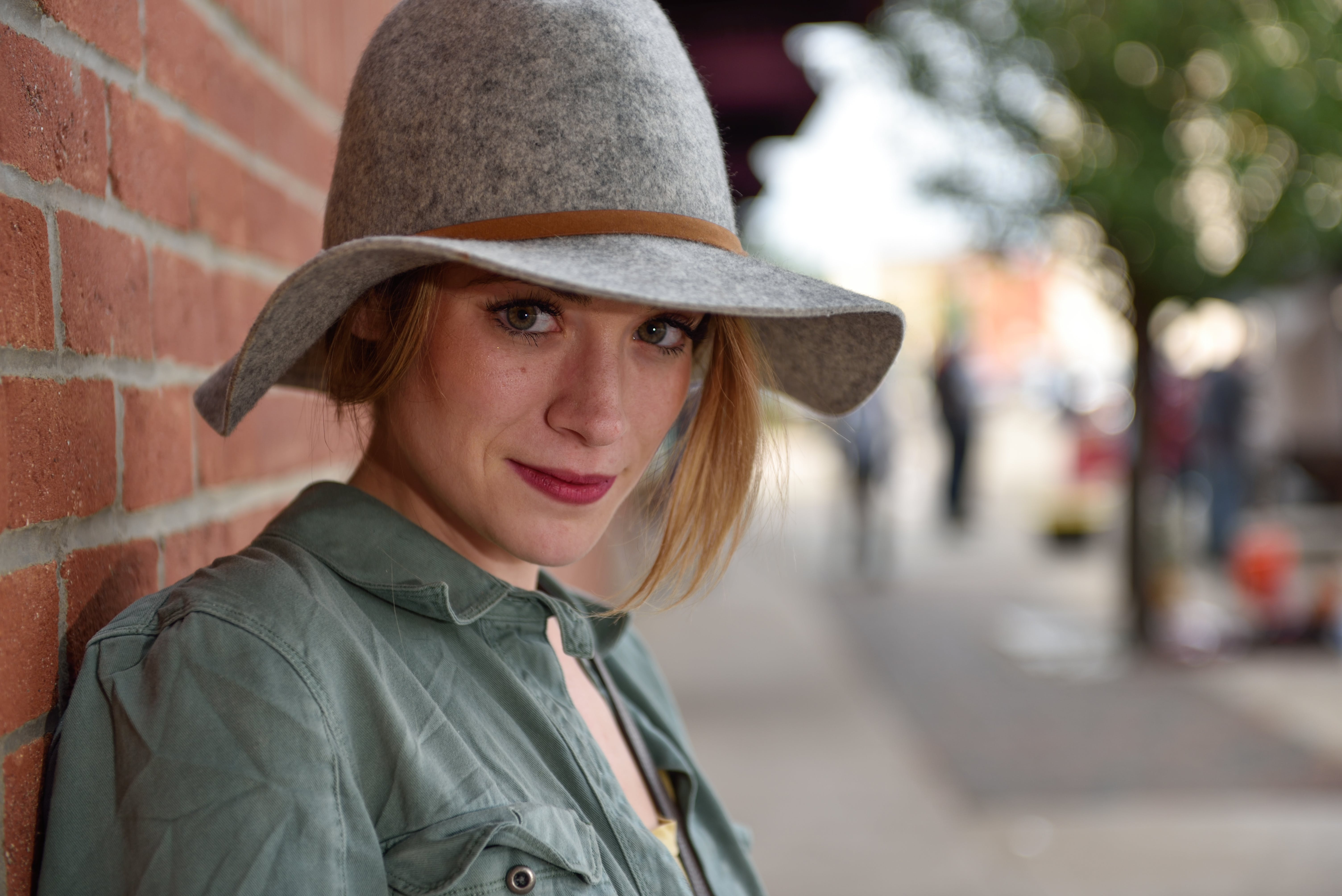 Selective Focus Photography of Woman in Blue Button-up Shirt and Gray Sun Hat Leaning on Brown Brick Wall
