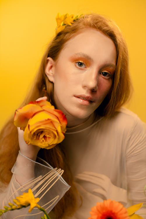 Woman in White Long Sleeve Shirt Holding Orange Rose