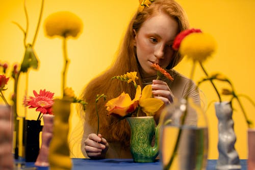 Girl Holding Yellow Flower in Green Glass Vase