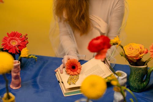 Woman in White Long Sleeve Shirt Holding Red and Yellow Flowers