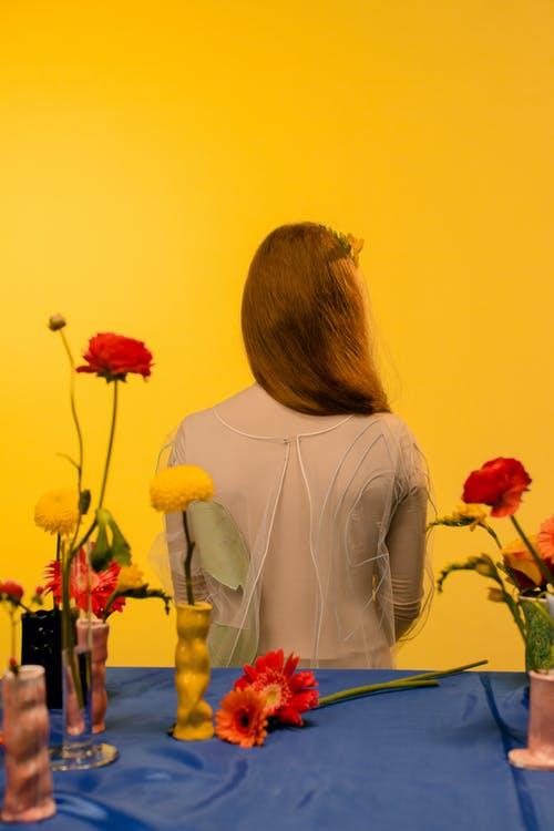 Woman in Gray Long Sleeve Shirt Holding Red and Yellow Flowers