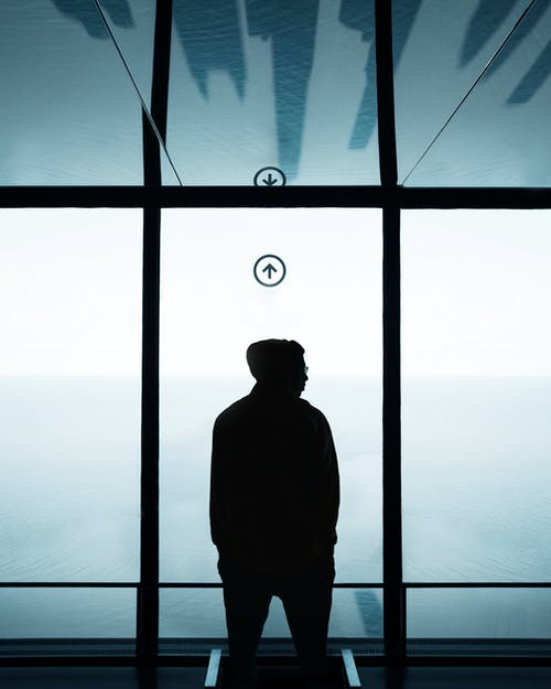 Silhouette of Man Standing in Front of Window