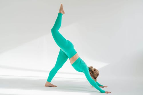 Full body side view of unrecognizable active female in activewear doing Eka Pada Adho Mukha Shvanasana posture on white background in studio