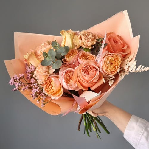 From above of fresh roses arranged in romantic bouquet in hand of anonymous florist in studio