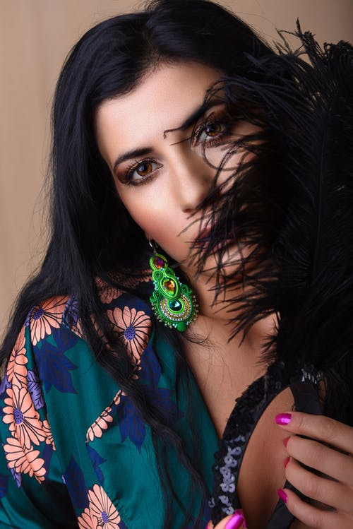 Calm woman with dark hair and makeup in stylish clothes covering face with dark feathers and looking at camera against beige background