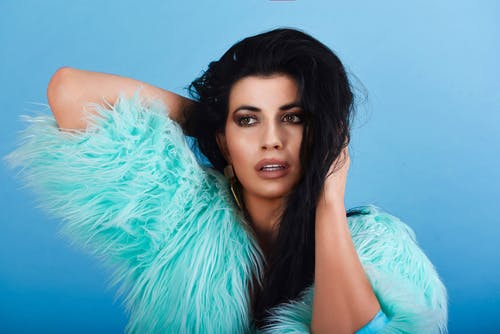Pensive female with long dark hair and makeup in trendy clothes touching head and looking away against blue background in studio