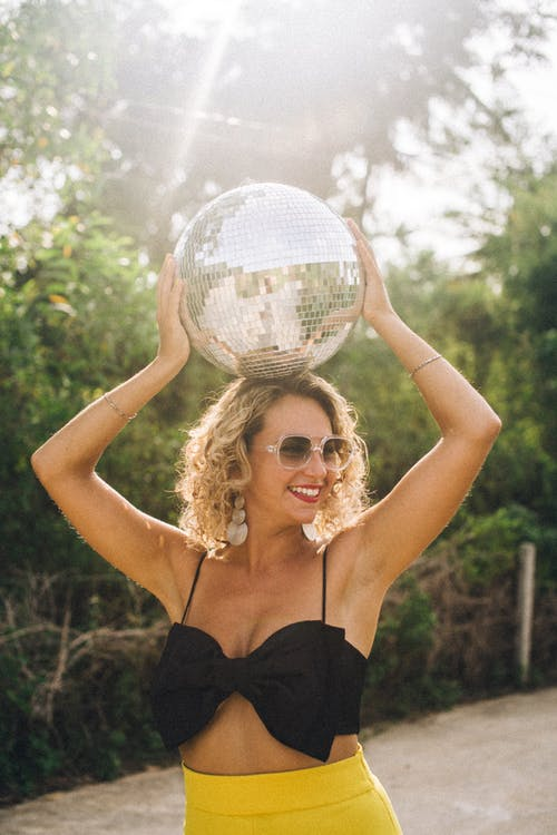 Woman in Black Top Holding a Mirror Ball Over Head