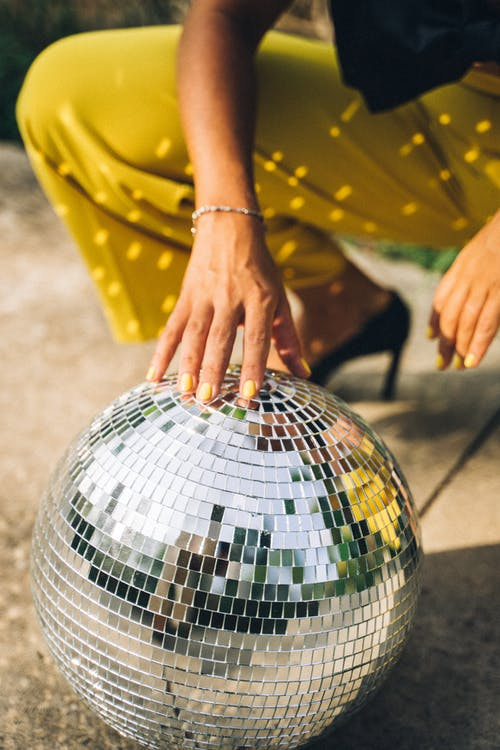 Person Resting Hand on Mirror Ball