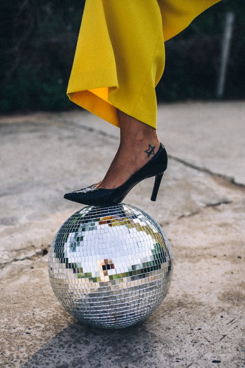 A Woman Stepping on a Disco Ball