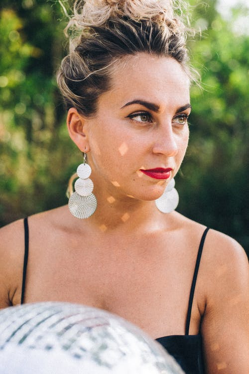 Woman in Black Spaghetti Strap Top With Silver Earrings