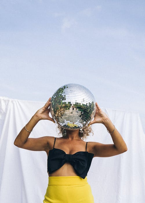 Woman in Black Top Holding a Mirror Ball on Face