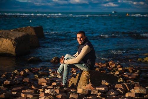Man Sitting on Stone Under the Blue Sky