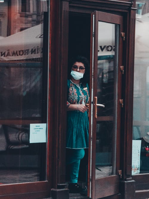 Woman  Wearing Face Mask Opening a Glass Door